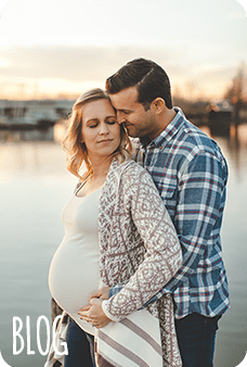 Pregnant woman with husband by lake at sunset
