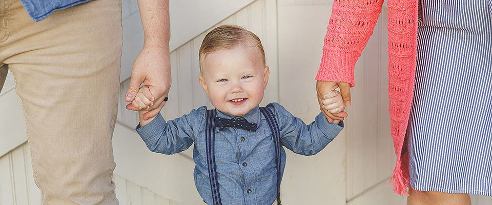 A smiling toddler boy in blue and suspenders holding the hands of his parents