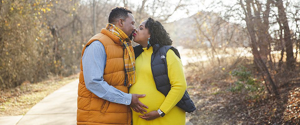 a black couple with a pregnant woman, kissing while wearing bright, winter clothing