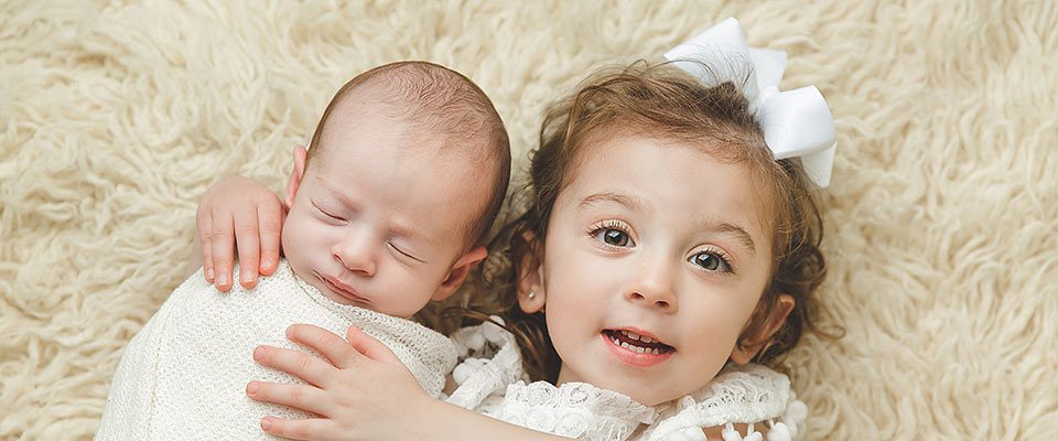 a white newborn boy and toddler girl on a cream colored rug.