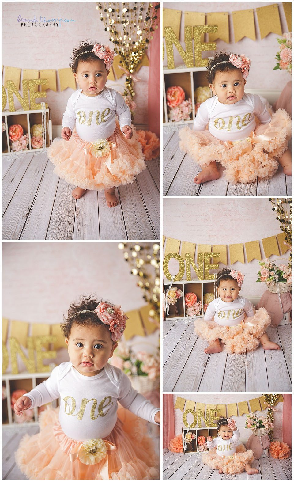 studio cake smash session with pink, peach, white and gold, and flowers. A medium skinned baby girl with curly brown hair