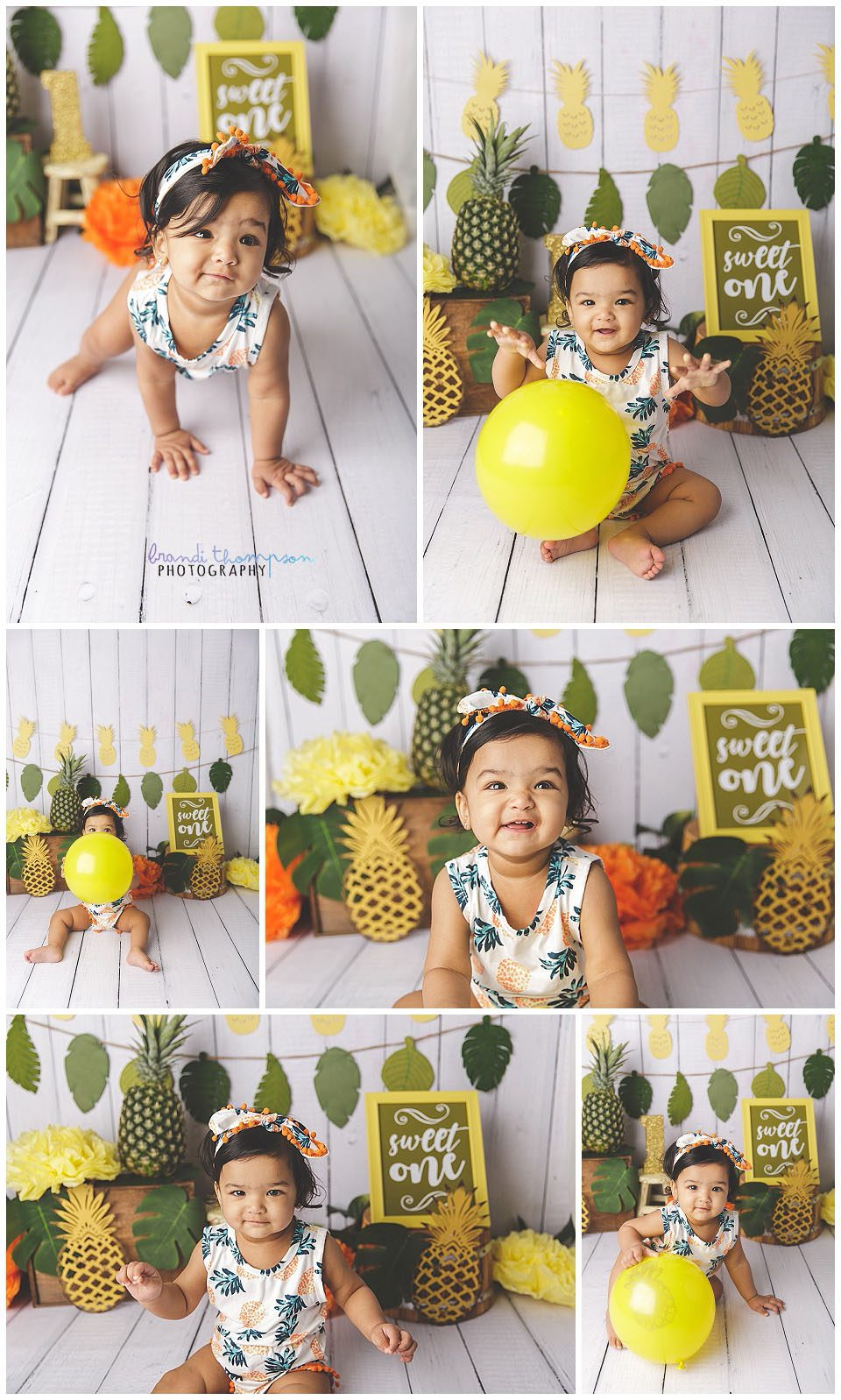 one year old baby girl in studio with white plank backdroop and tropical pineapple decorations